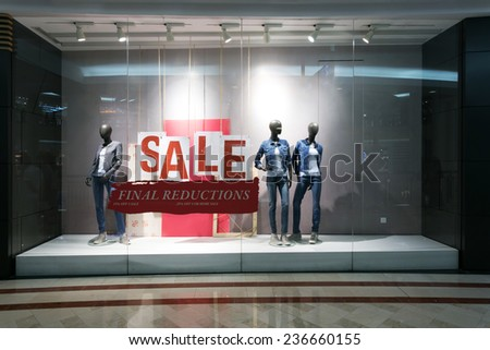 fashion clothes shop display window and sale sign. - stock photo
