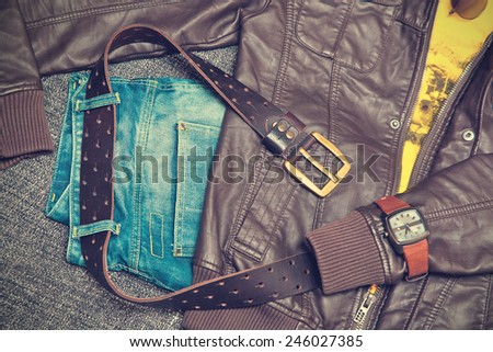Fashion concept. Clothing items: leather twist, jeans, T-shirt, belt, watch and bracelet. Vintage style - stock photo
