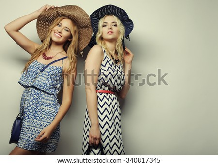 fashion concept: two sexy young women in summer fashion dress and straw hats, studio background - stock photo