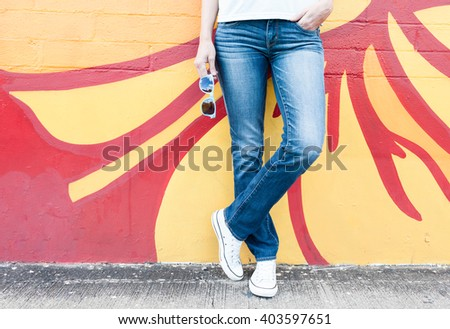 Fashion concept. Young woman with jeans and holding sunglasses against a colorful background.  - stock photo