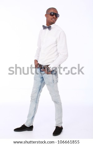 Fashion conscious young African American business man or student wearing jeans,smart black shoes,long white shirt sunglasses and a silver bow tie and has his hands placed in his pockets looking right