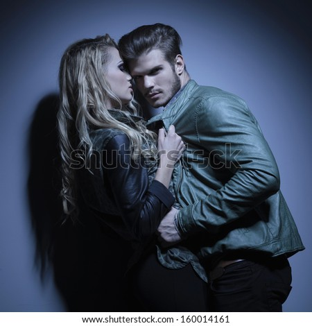 fashion couple in leather jackets pulling each other closer, man looking at the camera - stock photo