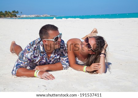 Fashion couple relax on a Caribbean beach at Cap Cana, Dominican Republic. Lovers dreaming and thinking looking happy, smiling cheerful. Outdoors, lifestyle. - stock photo