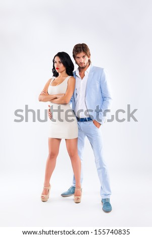Fashion couple unhappy serious negative emotion, men wear blue suit and woman sexy dress high heel shoes, full length over gray background