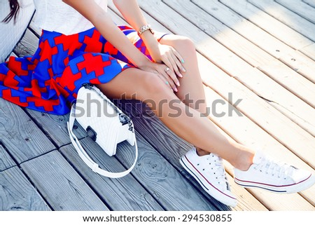 Fashion Crop photos.Female feet in white sandals with heels.stands on the edge of the pool on wooden floor.Stylish image of trendy silver summer sandals.heels,summer accessory,nails,sunset background - stock photo