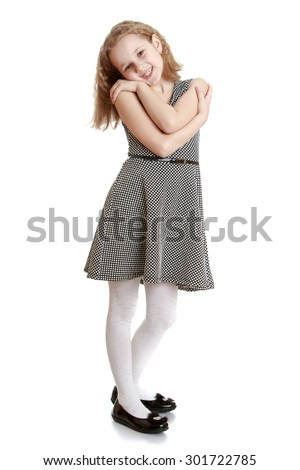Fashion delicate blonde girl in a gray short dress. The girl gently looks into the camera clasping their shoulders-Isolated on white background - stock photo