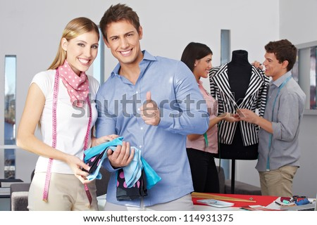 Fashion design student holding thumbs up with other people at work