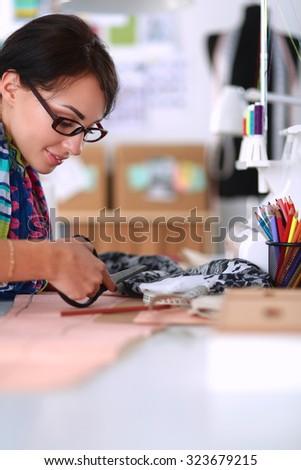 Fashion designer cutting textile next to a sewing machine  - stock photo