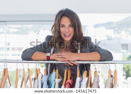 Fashion designer leaning on clothes and smiling to the camera - stock photo