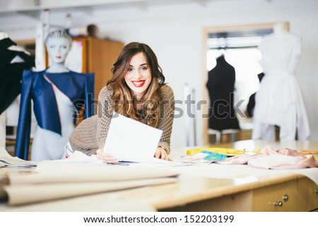 Fashion designer looking at sketches in studio - stock photo