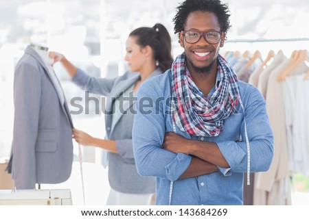 Fashion designer posing while his colleague is measuring blazer lapel behind - stock photo