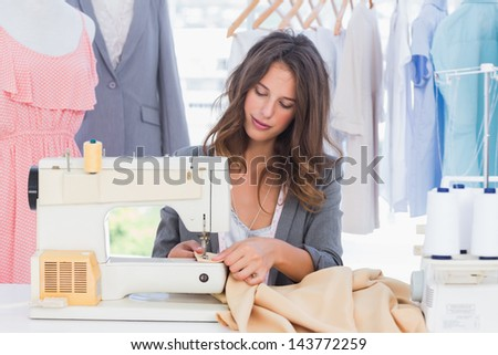 Fashion designer sewing with sewing machine - stock photo