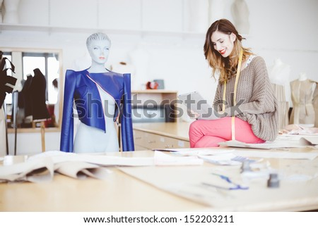 Fashion designer using tablet computer in studio - stock photo