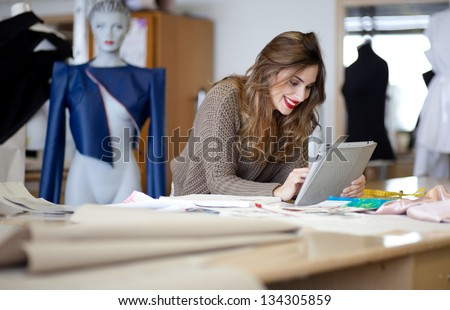 Fashion designer using tablet computer in the studio - stock photo