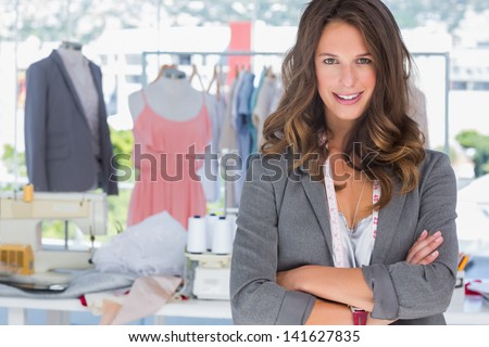 Fashion designer with arms folded in a bright creative office - stock photo