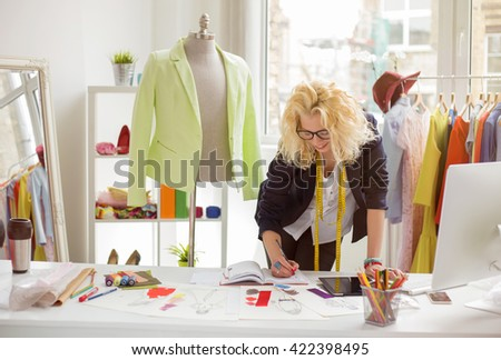 Fashion designer working in sketch at her creative office - stock photo