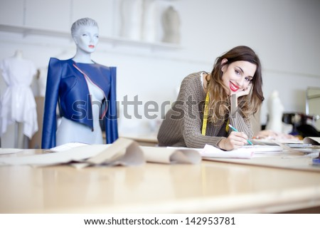 Fashion designer working on designs in the studio - stock photo