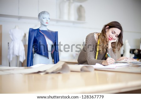 Fashion designer working on her designs in the studio - stock photo