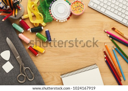 Fashion designer workspace top view. Sewing equipment, colored pencils, laptop and notepad on wooden table with copy space