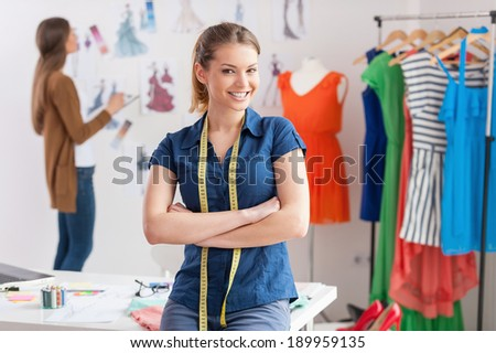 Fashion designers at work. Beautiful young woman with measuring tape on shoulders looking at camera and smiling while her colleague standing on background  - stock photo