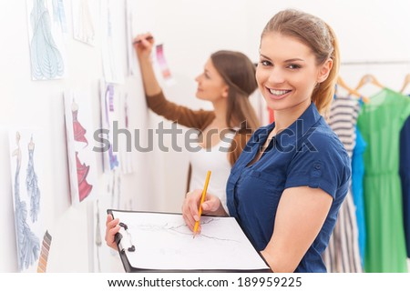 Fashion designers sketching. Beautiful female fashion designer holding clipboard with sketches and smiling while her colleague standing on background