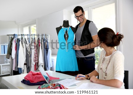 Fashion designers working on creation in workshop - stock photo