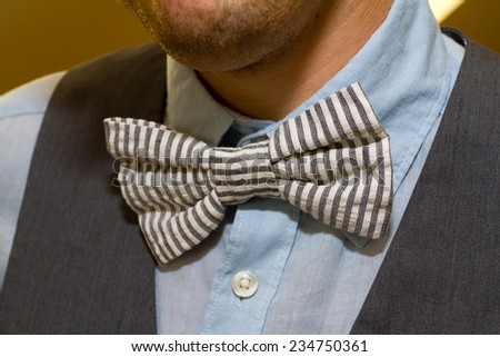 Fashion detail image of a groom wearing a bowtie on his wedding day. - stock photo