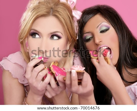 fashion doll beautiful girls eating diet sweet on pink background - stock photo