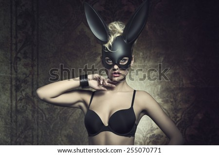 fashion Easter creative portrait of mysterious woman with blonde curly hair-style and lack bra posing with cute dark bunny mask. Fetish atmosphere