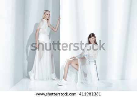Fashion editorial shot in studio with white background. Two beautiful model posing in total white clothes. - stock photo