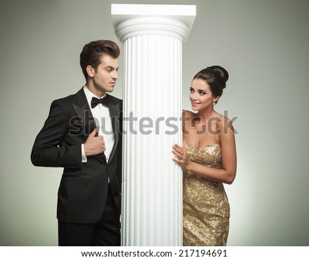 fashion elegant couple looking at each other near column in studio - stock photo