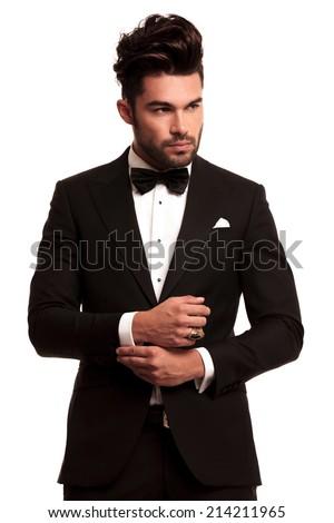 fashion elegant man in tuxedo fixing his sleeve on white background - stock photo