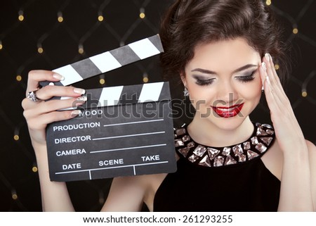 Fashion elegant woman posing with sexy red lips holding cinema clap. Super star model shot. Happy smiling girl.