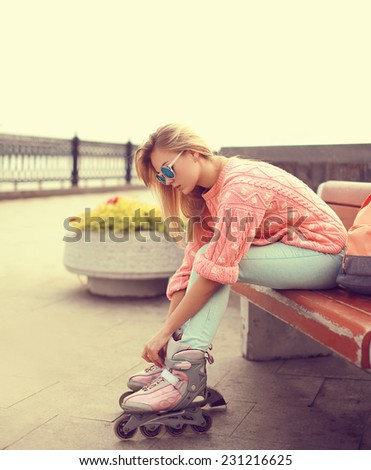 Fashion, extreme, youth and people concept - pretty stylish blonde with roller skates in the city park, cool roller girl outdoors  - stock photo
