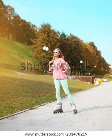 Fashion, extreme, youth and people concept - pretty stylish hipster girl rollerblading in the city park, cool roller girl outdoors - stock photo