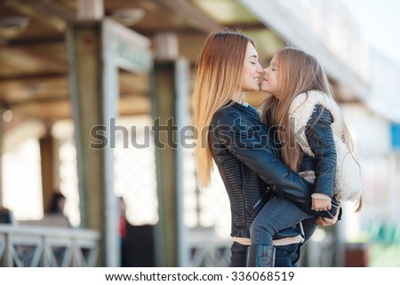 Fashion family concept - stylish mother and child wear. A portrait of a happy family: a young beautiful woman with her little cute daughter. Young daughter hugs mother in autumn city outdoor - stock photo