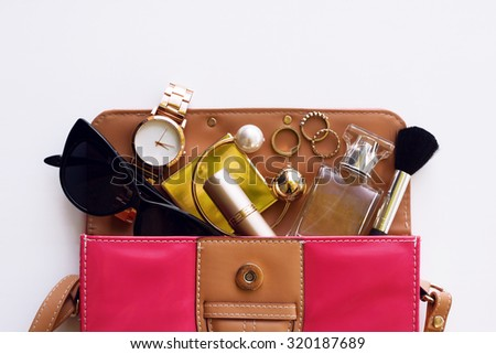Fashion female accessories gold watch black sunglasses lipstick perfume and red handbag. Overhead of essentials for modern girl. - stock photo