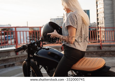 Fashion female biker girl. Young Blonde woman in leather jacket sitting on vintage custom motorbike. Outdoors lifestyle portrait - stock photo