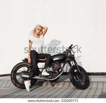 Fashion female biker girl. Young Blonde woman in leather jacket sitting on vintage custom motorbike. Outdoors lifestyle portrait - stock photo