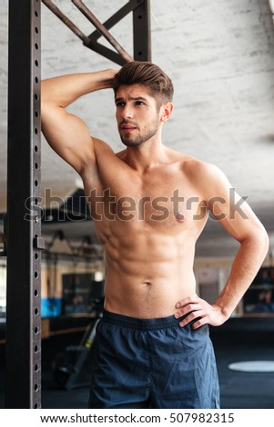 Fashion fitness man in gym. looking away