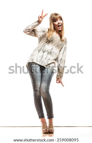 Fashion. Full length happy woman jeans pants showing victory hand sign gesture isolated - stock photo