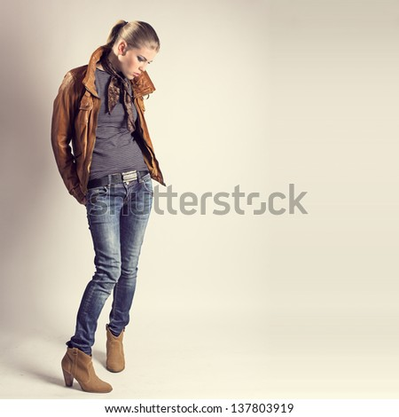 Fashion girl. Beautiful glamour stylish model in leather jacket, neckerchief, jeans, high heels. Young Caucasian woman posing in studio. - stock photo