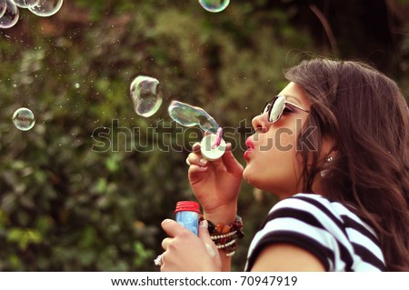 Fashion girl blowing bubbles in the wind