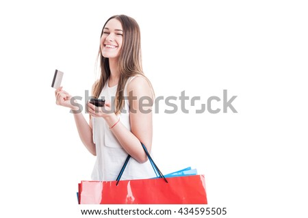 Fashion girl buying online holding cellphone and credit card with colorful shopping bags isolated on white background with copy space - stock photo