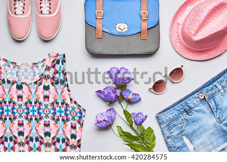 Fashion girl clothes accessories set. Stylish hipster, trendy handbag, top, denim, gumshoes, pink hat, sunglasses and flowers. Bright urban summer outfit. Unusual overhead, top view on gray background - stock photo