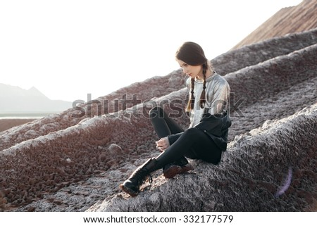 Fashion girl enjoying stunning views of the slope. Young sexy woman with braids dressed in a silver dress and leather jacket. Outdoors lifestyle portrait - stock photo