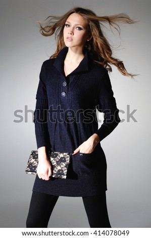 fashion girl holding little purse posing in the studio