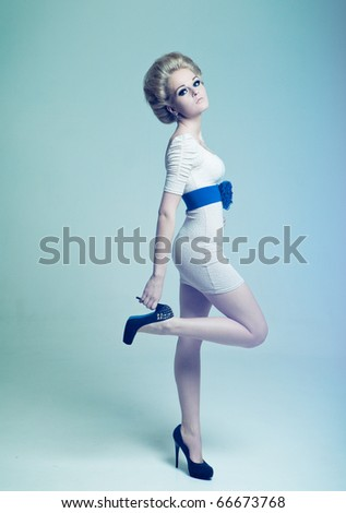 Fashion girl holding on to the heel - stock photo