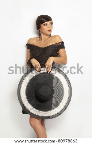 Fashion girl in a big hat in the studio