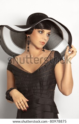 Fashion girl in a big hat in the studio - stock photo